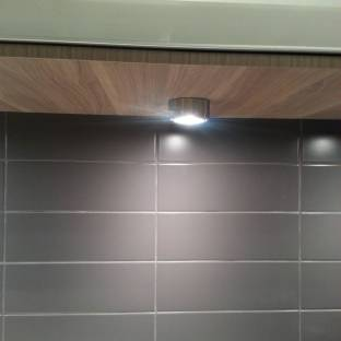Protruding downlights beneath overhead cabinets are not very appealing; opt for flush mounted lights or LED strips instead.