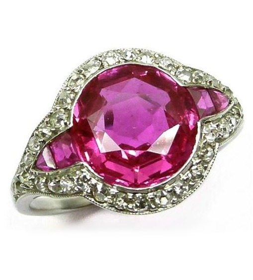 Burmese pink sapphire and diamond cluster ring. Cartier, circa 1910.  One faceted 3.20 ct Burmese pink sapphire, flanked by tapered calibre cut pink sapphires.