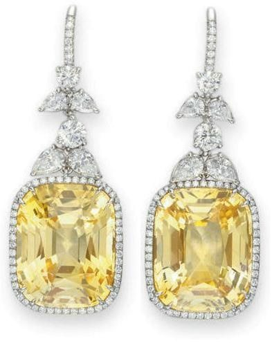 Yellow sapphire and diamond earrings. Each suspending a cushion-cut yellow sapphire, weighing approximately 14.03 and 13.83 carats.