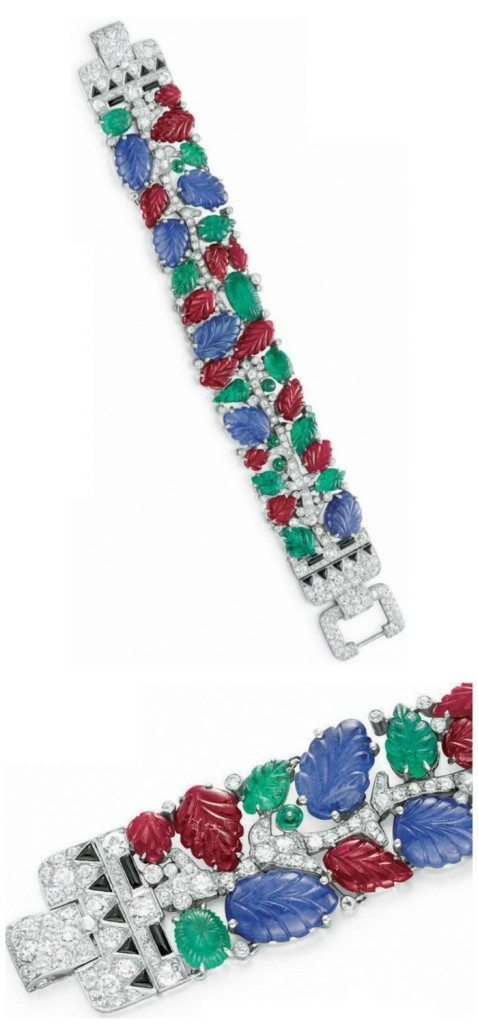 An Art Deco tutti frutti bracelet, by Cartier, circa 1930. Designed as a diamond vine and set with carved ruby, sapphire and emerald leaves, and emerald bead berries.