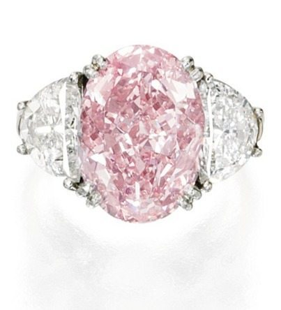 A pink diamond and diamond ring, Oscar Heyman and Bros. An oval-shaped Fancy Intense Pink diamond (6.54 carats), flanked by 2.21 carats of white diamonds. Via Diamonds in the Library.