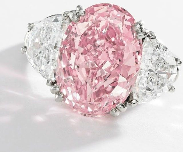 Pink diamond and diamond ring, Oscar Heyman and Bros. An oval-shaped Fancy Intense Pink diamond (6.54 carats), flanked by 2.21 carats of white diamonds. Via Diamonds in the Library.