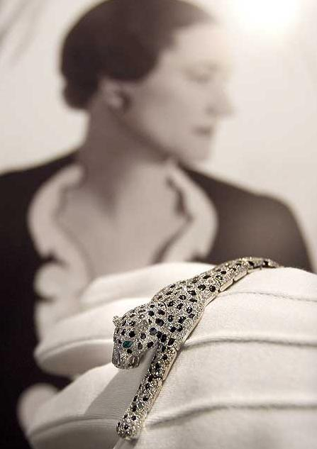 Here, the Duchess of Windsor's Cartier panther bracelet is displayed by a Sotheby's employee in front of a portrait of the Duchess.