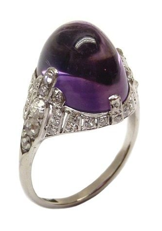 Art Deco amethyst and diamond ring, circa 1925. A large, oval cabochon amethyst set in a tapered frame set with diamonds, in platinum. Via Diamonds in the Library.