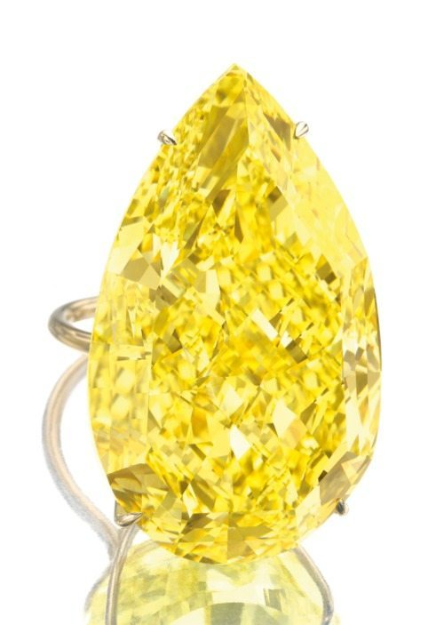 The Sun Drop diamond, a legendary 110.03 carat fancy vivid yellow pear-shaped diamond, shown here mounted on a gold ring setting. Via Diamonds in the Library.