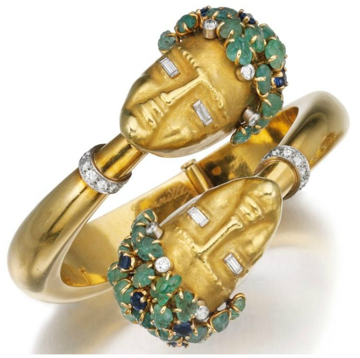 Bangle by Cannilla, Masenza. Made of gold and designed with two ladies' heads. Each head is set with carved emeralds, sapphires and diamonds.  Accompanied by a matching ring.