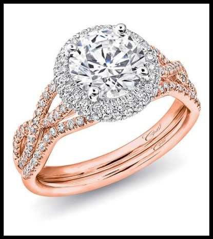 This Coast diamond rose gold engagement ring features a twisted splint shank design and a white gold diamond halo around the 1.5 carat center stone. Shown with matching band. Via Diamonds in the Library.