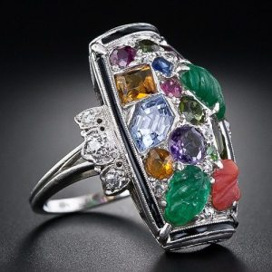 Tutti-frutti Art Deco dinner ring, circa 1925. An unusual design incorporating carved emeralds, sapphires, rubies, amethysts, citrines, and diamonds within a border of black enamel. Via Diamonds in the Library.