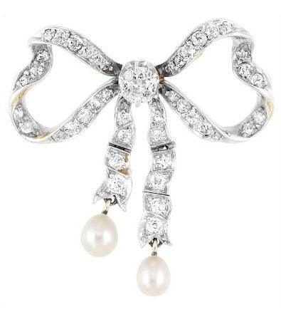 Antique diamond and pearl bow brooch, circa 1905. Made of gold and is set with one old European-cut diamond (.50 ct.), 42 old European-cut diamonds (1.25 cts.), and 2 pearls. Via Diamonds in the Library.