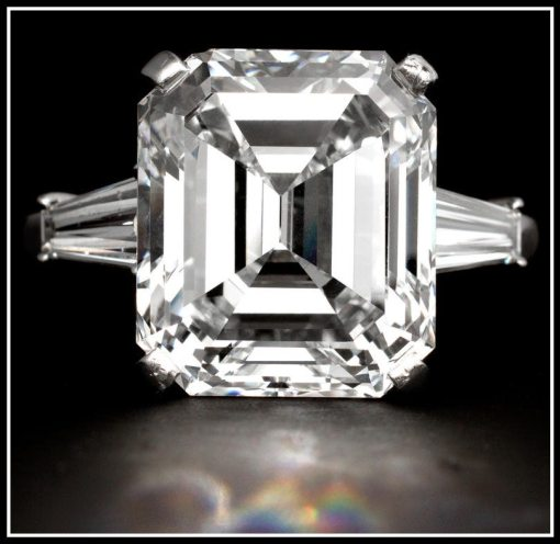 Diamond engagement ring with a 10.48 carat cut-cornered rectangular-cut diamond flanked on either side by a tapered baguette-cut diamond. Via Diamonds in the Library.