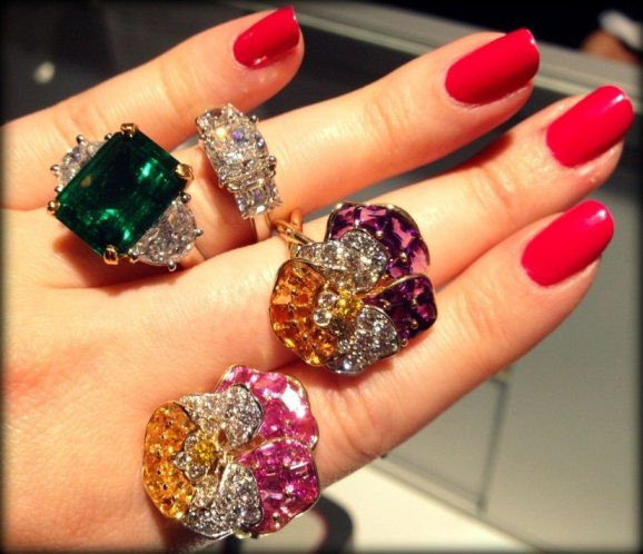 A hand full of Oscar Heyman: two diamond and gemstone pansy rings, one diamond engagement ring and one emerald and diamond ring. Via Diamonds in the Library.