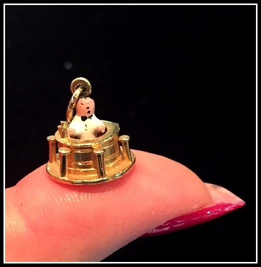 Antique gold charm with a tiny bartender at a tiny bar