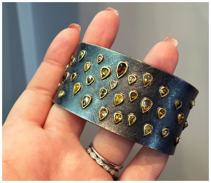 A stunning cuff bracelet from Todd Reed with teardrop-shaped colored diamonds set in gold bezels