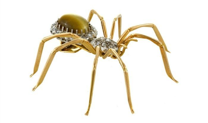 A spider brooch in gold with a tiger's eye body and diamond embellishments.
