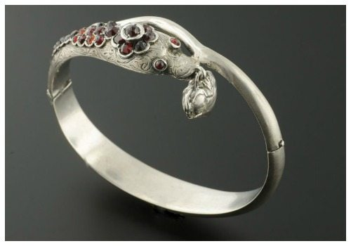 An antique Victorian snake bangle in sterling silver with garnets.