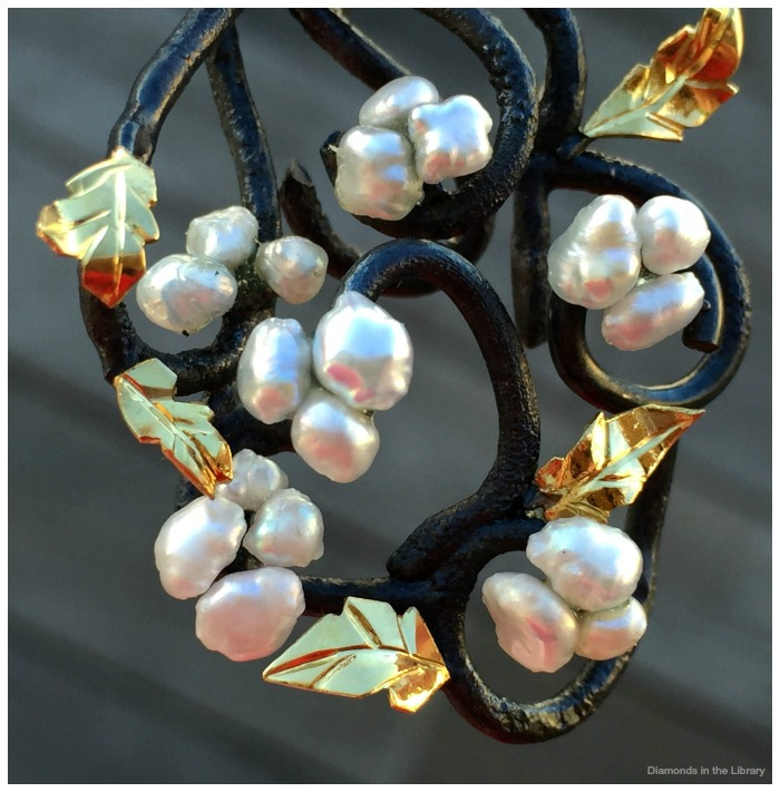 Detail of a pair of earrings by Brenda Smith, with cultured pearls and 22k gold leaves on silver.