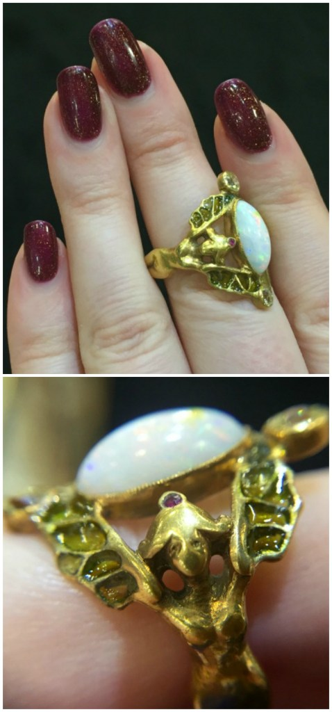 Detail of a beautiful antique gold Art Nouveau ring with a design of two women with plique-a-jour enamel wings supporting an opal. At Michael Longmore.