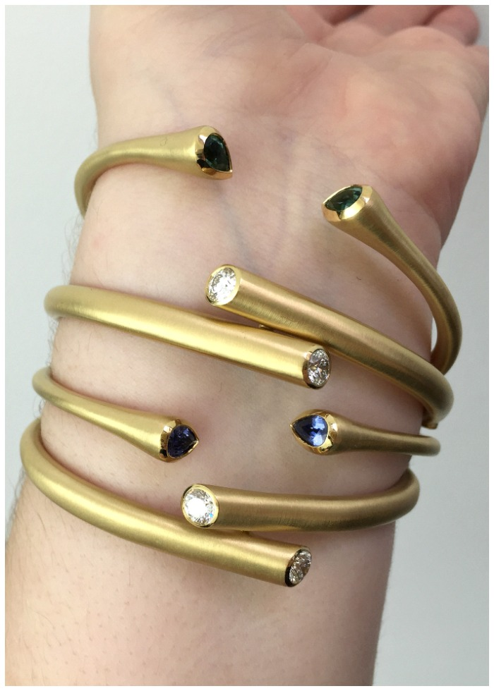 A stack of fabulous whirl bracelets from Carelle. Gold with gemstones.