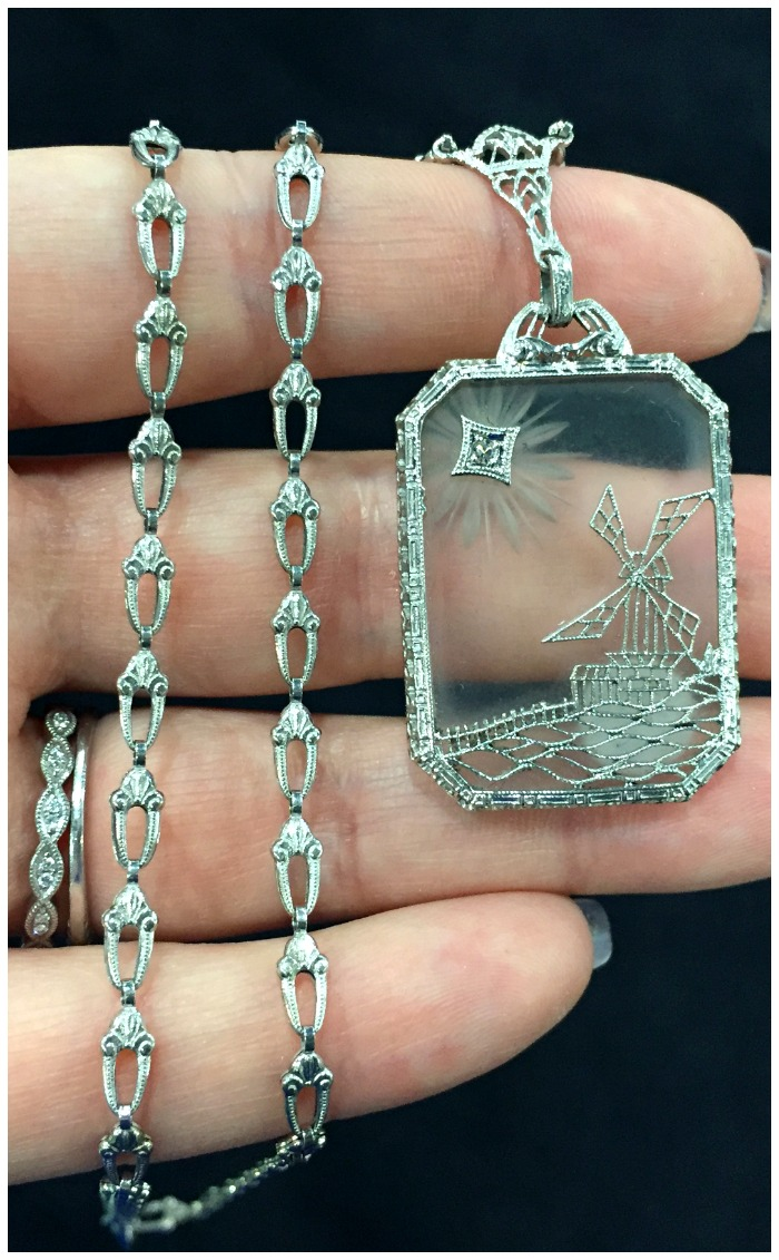 An unusual and extraordinary camphor glass pendant with the original chain. Filigree detail in a windmill motif. Antique; Art Deco era.