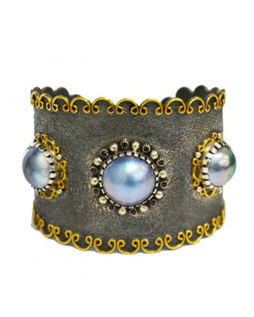 A sterling silver cuff bracelet by Stella Flame, with pearls, gemstones, and gold filigree.