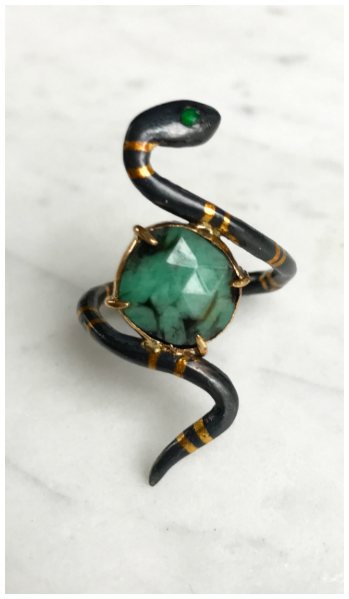 A beautiful snake ring in oxidized sterling silver and gold with green gems. By Acanthus.