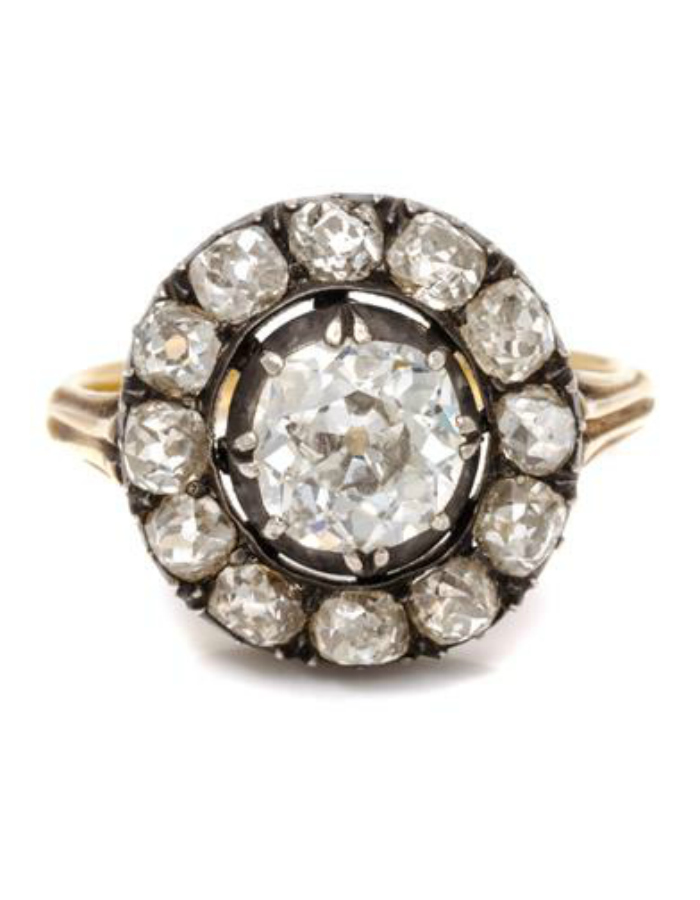 An antique silver topped gold and diamond ring, containing one old mine cut diamond (approx 1.15 carats) and 12 old mine cut diamonds (approx 1.44 carats total).