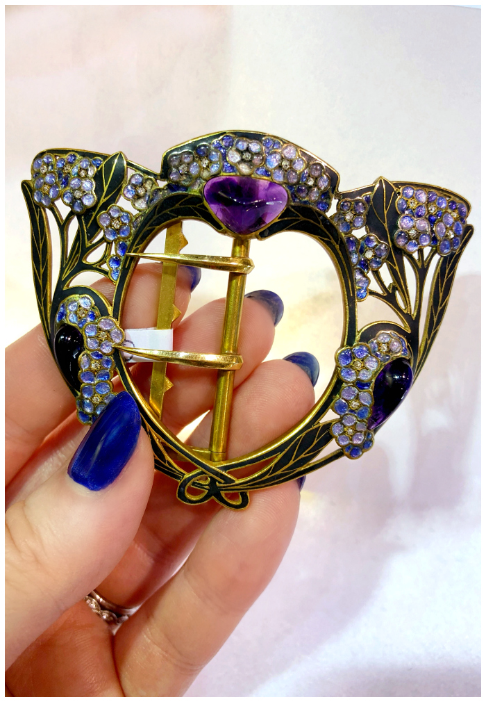 A beautiful Art Nouveau era belt buckle with amethyst and enamel detailing. Spotted at Ishy Antiques.