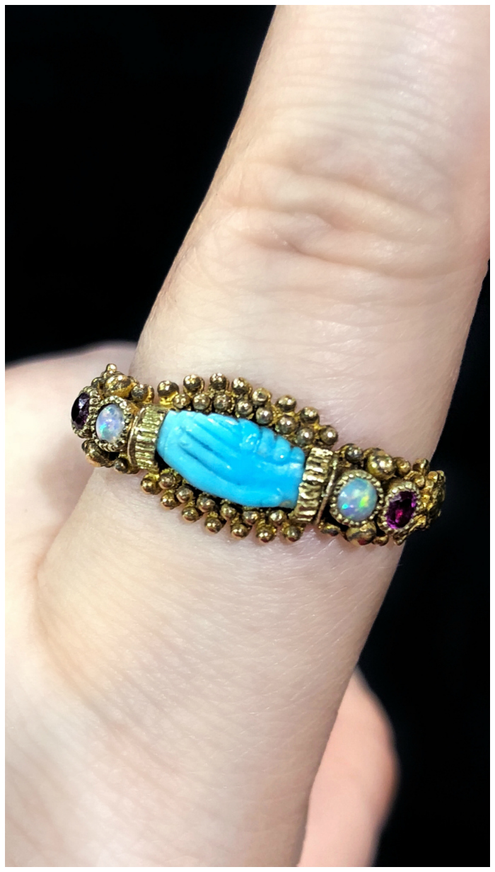 An extremely rare antique fede ring in gold, featuring gems and a carved turquoise pair of hands. From The Spare Room.