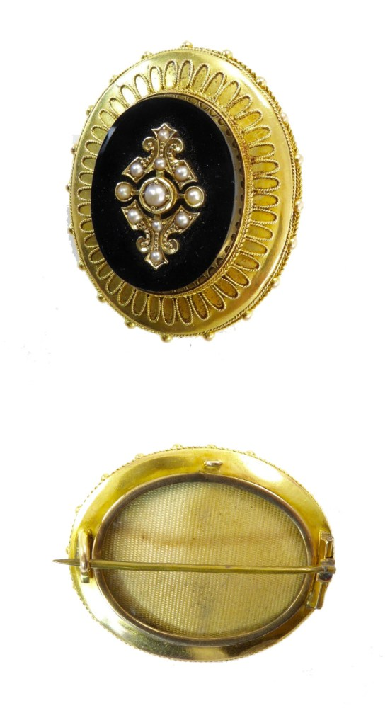 A Victorian era archaeological revival brooch in gold, with onyx and seed pearls. From Lisa Kramer Vintage.
