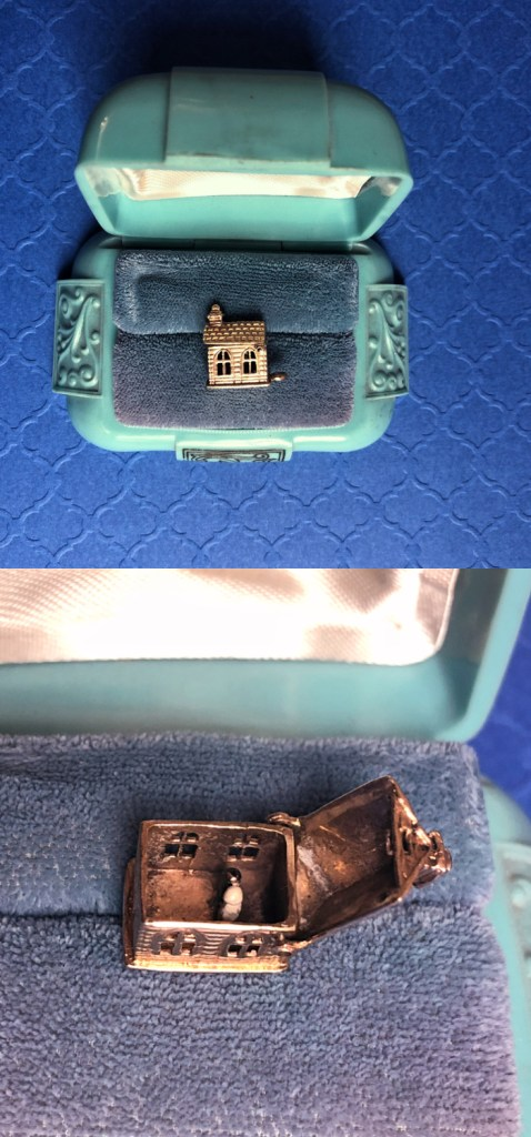 A wonderful vintage charm of a chapel or church. It opens to show a tiny bride and groom!! From Wilson's Estate Jewelry.