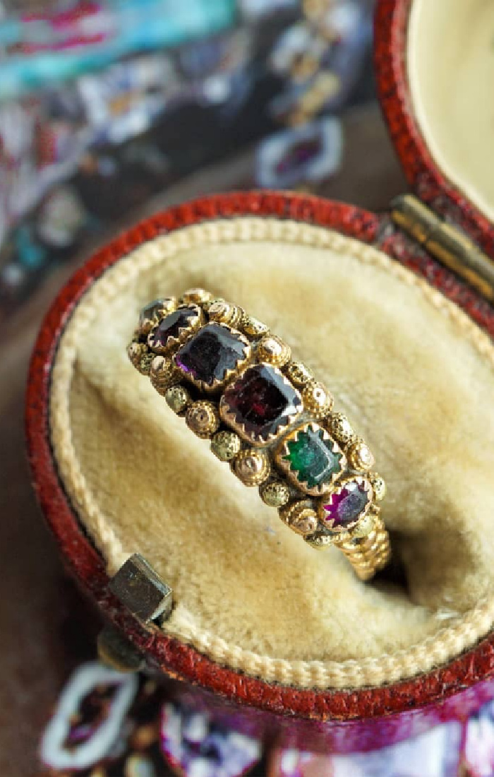 An antique Georgian acrostic ring with rose and green cannetille details. The gems spell out REGARD, a secret message of love. From Nalfies.