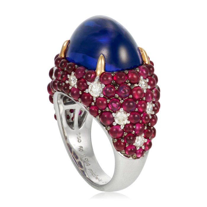 Michele della Valle tanzanite ring with a 17.19 carat cabochon tanzanite, round cabochon rubies, round diamonds, and 18k white and yellow gold