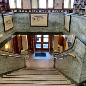 Looking down to double wooden doors, marble steps, brass handrails, surrounded by green white marble, 3 photos of the library in frames , books in cases
