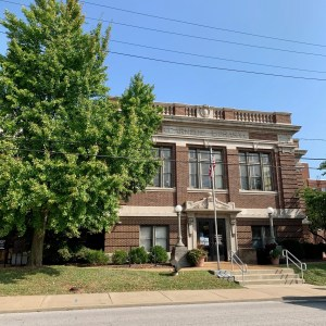 Carnegie Library brick building with 3 sets large windows on 2nd floor. Flagpole in front next to the steps, sidewalk and big leafy tree