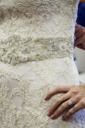 wedding dress and sash detail with engagement ring