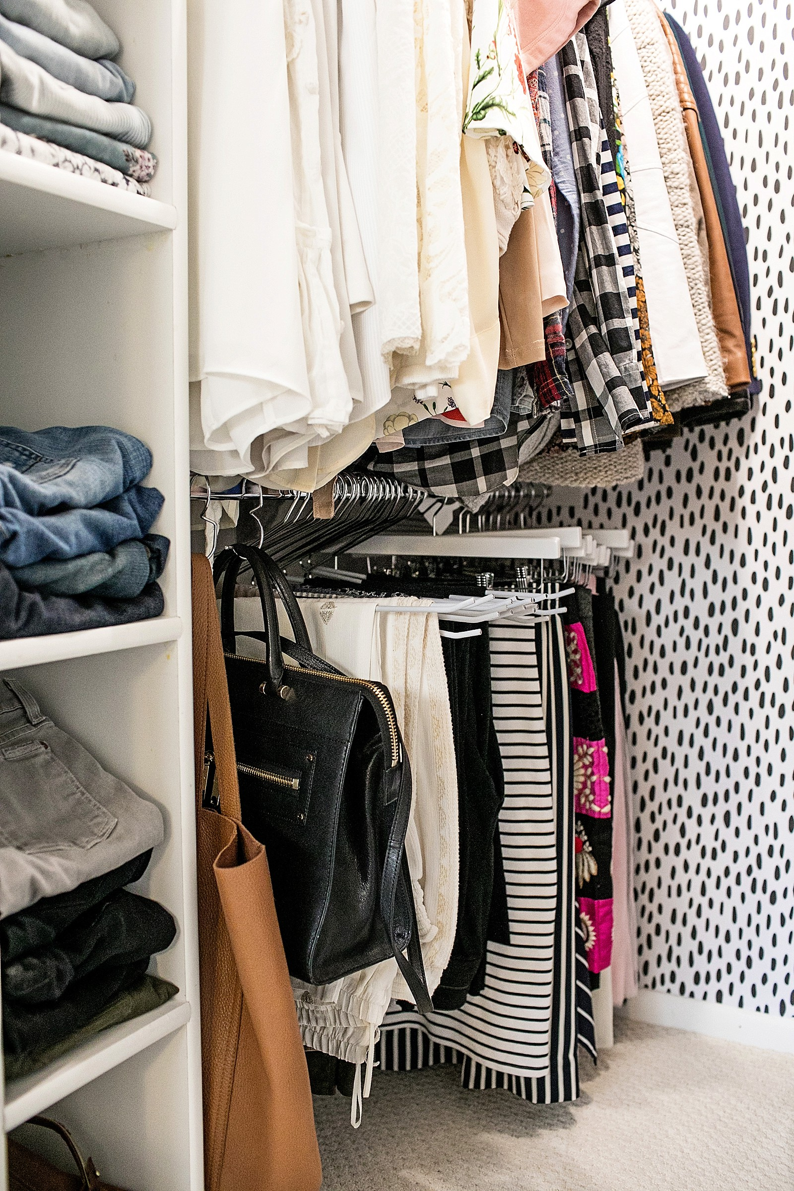 white wood pant hangers on chrome oval rods and purse hooks to keep a tiny closet organized