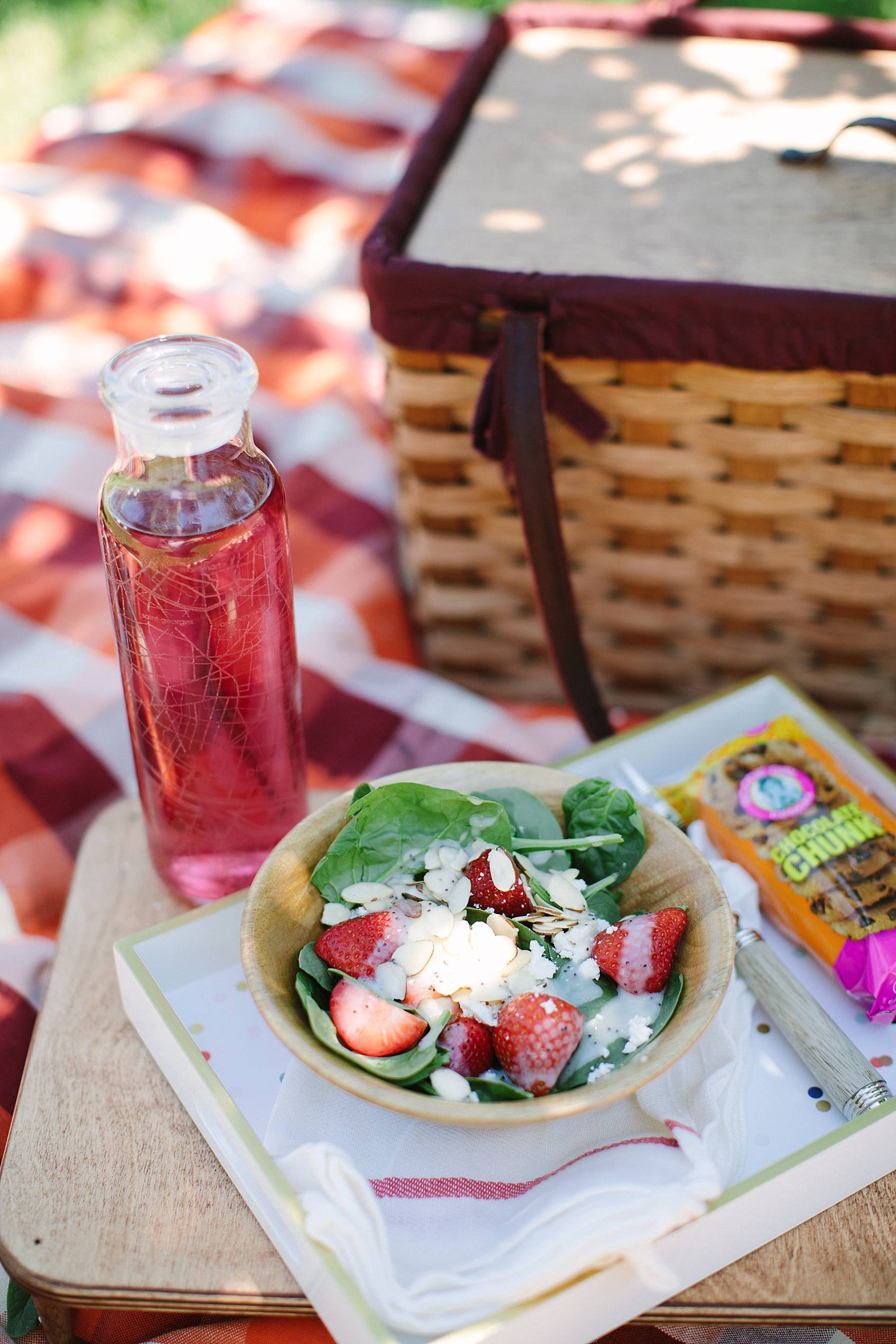 picnic basket in background on blanket featuring strawberry spinach salad with goat cheese
