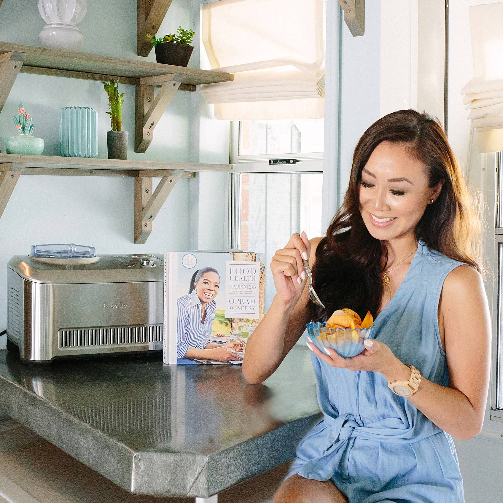 Blogger Diana Elizabeth sitting on stool eating peach sorbet she made with Breville smart ice cream maker
