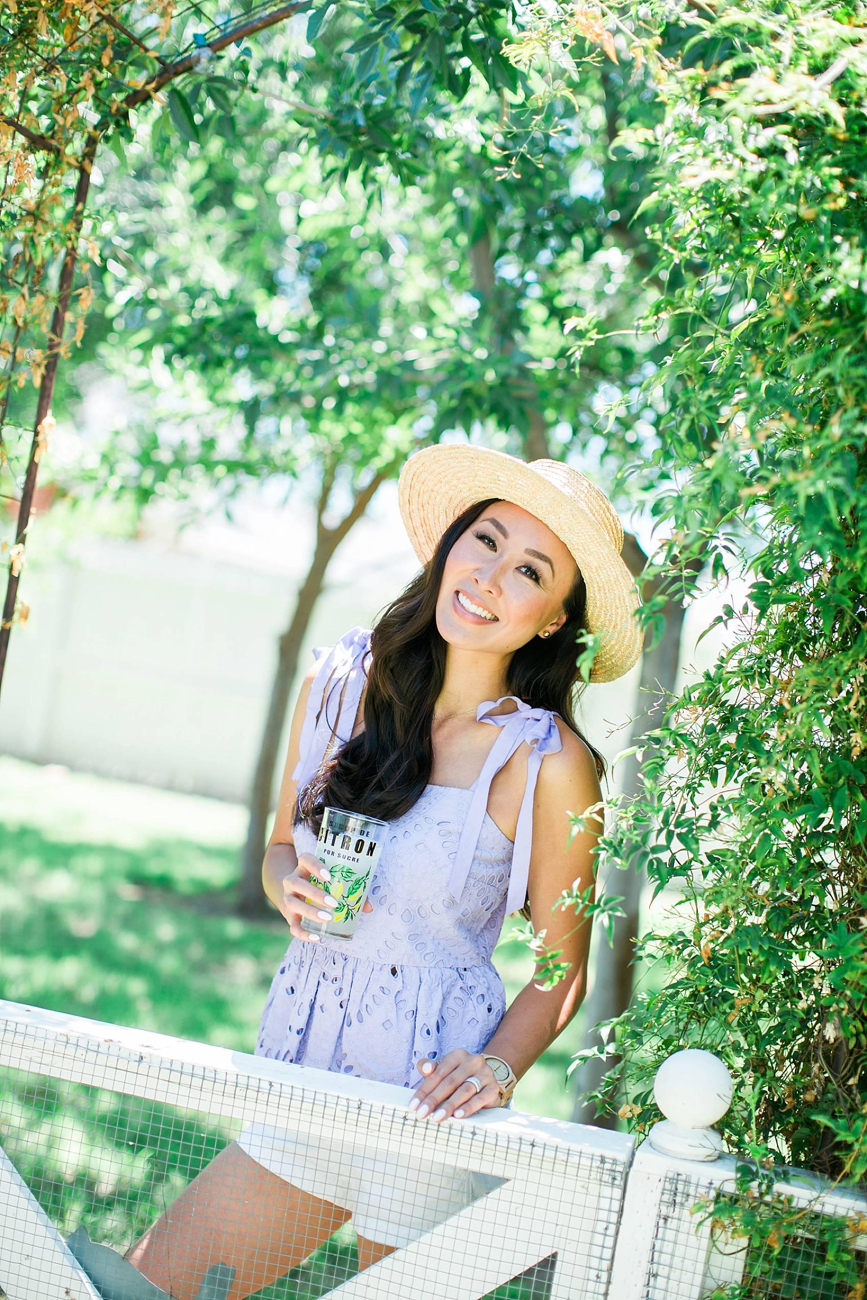 Lifestyle blogger diana elizabeth in purple eyelet top by j.crew in backyard jasmine vine wall holding glass of lemonade