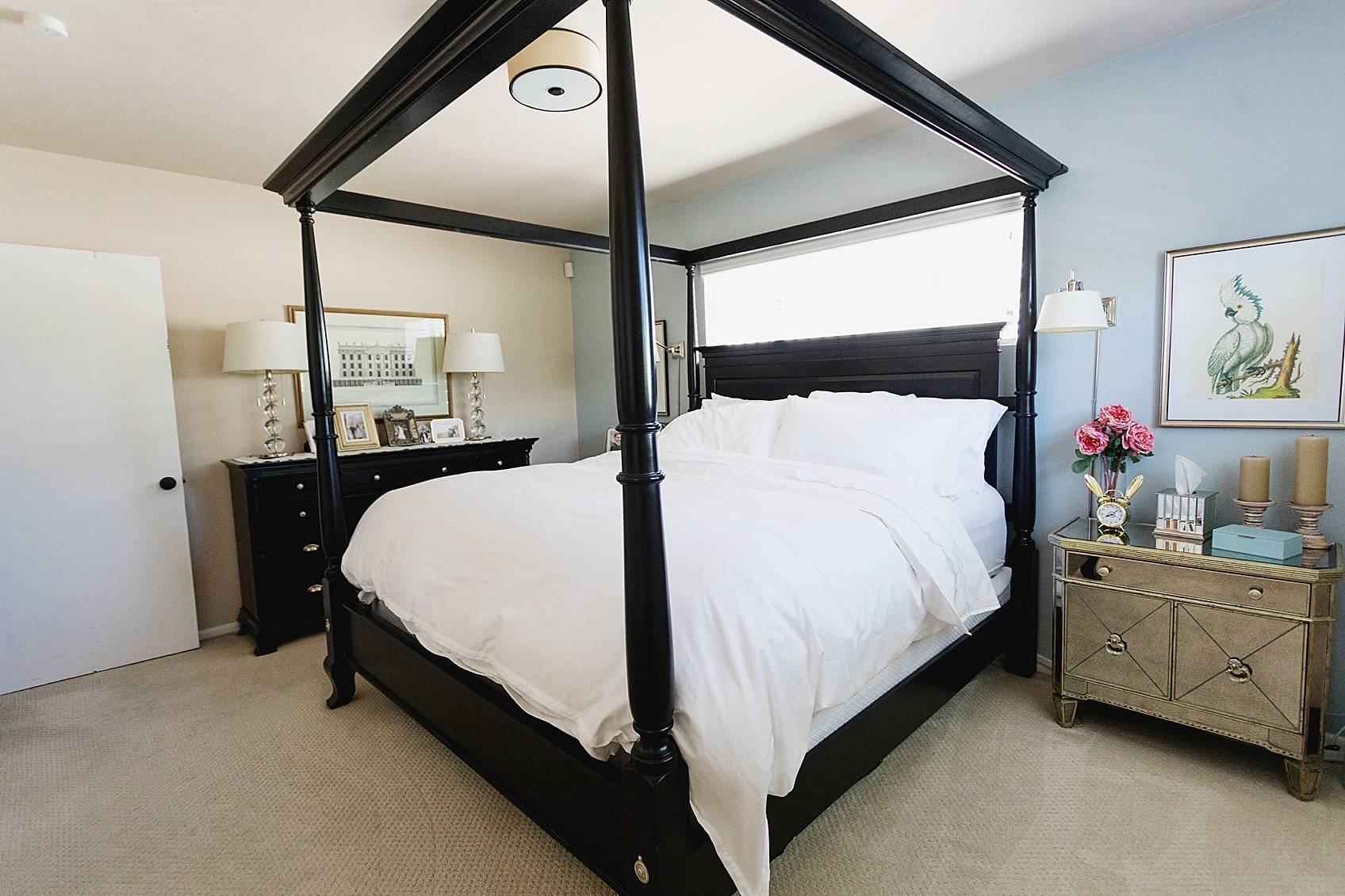 traditional bedroom with mirror nightstands black canopy bed with all white bedding white carpet