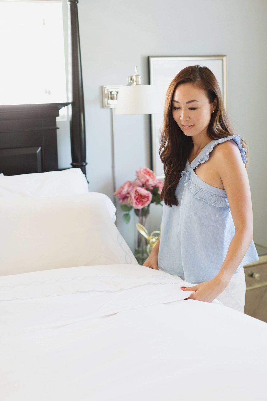 lifestyle blogger diana Elizabeth making the bed in her bedroom, all white bedding featuring Serena and lily duvet
