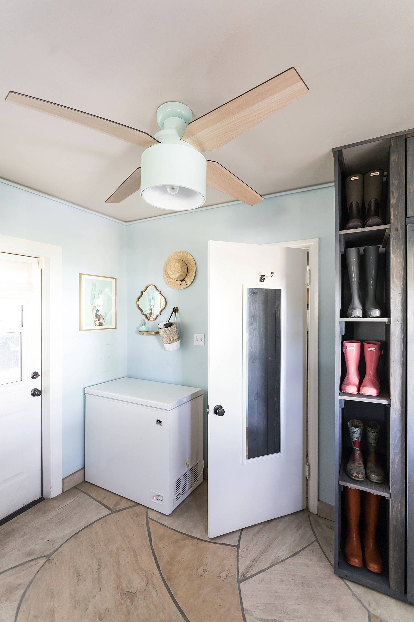 laundry mud room with custom cabinets rustic look with blue removable wallpaper in background and mint hunter fan Ikea cactus hunter boots display full length mirror