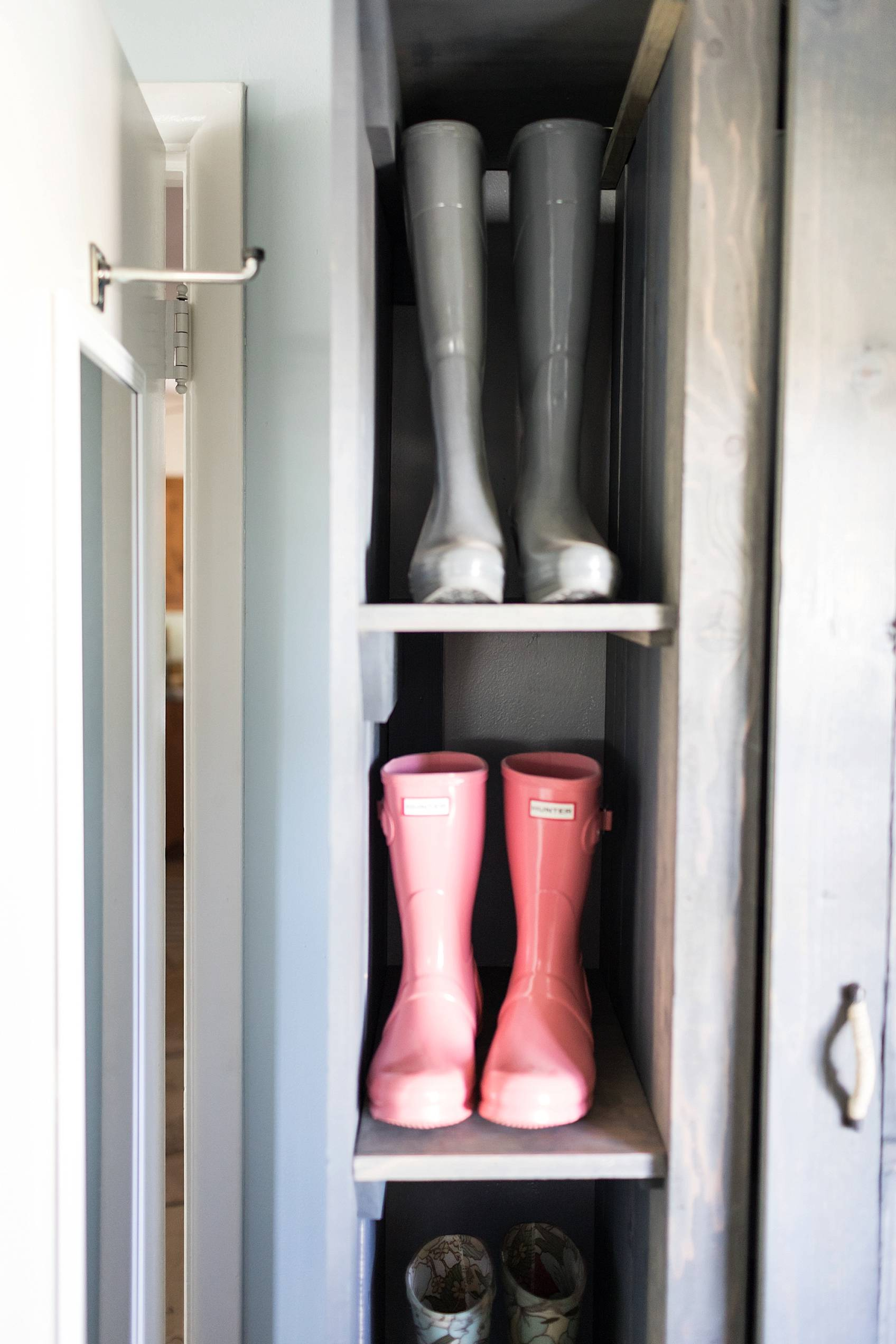 laundry mud room with custom cabinets rustic look with blue removable wallpaper in background and mint hunter fan Ikea cactus hunter boots display pink hunters