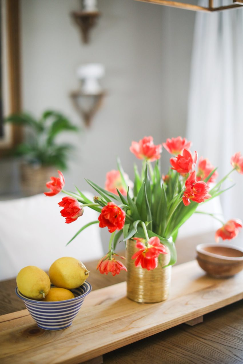 orange tulips in a gold vase