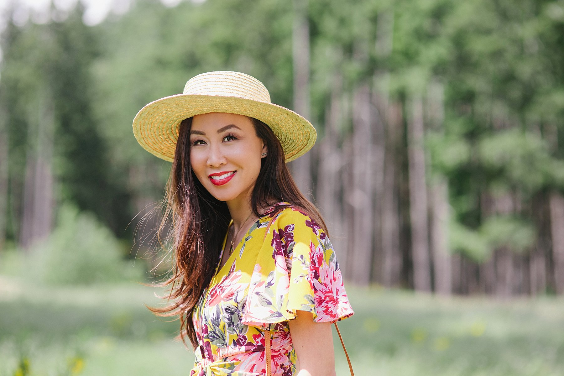 yellow floral jumpsuit by Tahari ASL on blogger Diana Elizabeth wearing straw boater hat and wicker tote standing in Bear Mountain in Victoria BC Canada