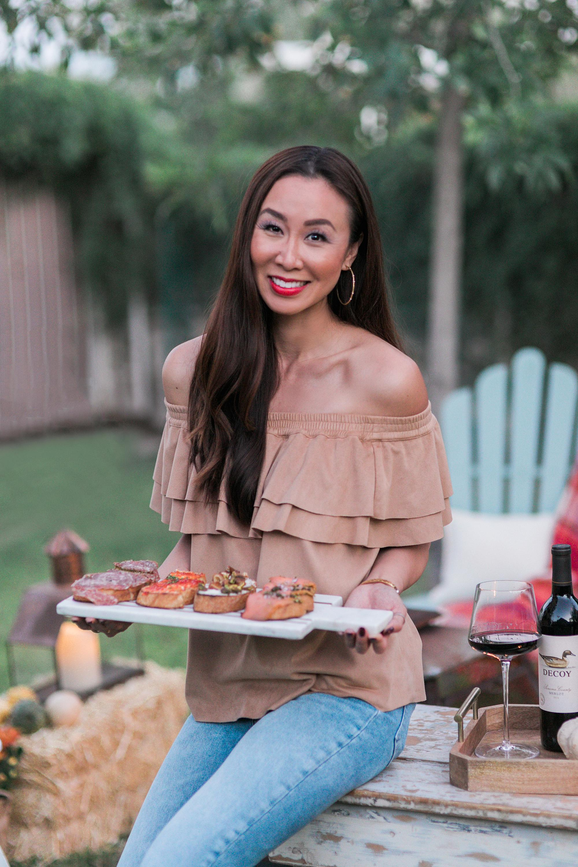 lifestyle entertaining hostess blogger Diana Elizabeth holding bruschetta board to pair with merlot decoy wine for outdoor backyard fall party #fallparty #wineparty