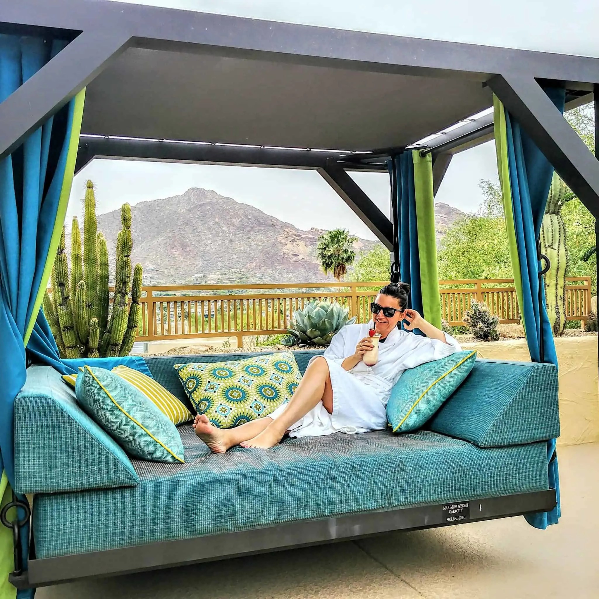 Marriott Cambelback Inn Scottsdale Arizona Spa lounge lounging on blue swing lounger with pina colada drink and mountain views in robe