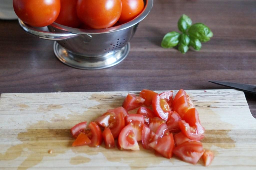 klein geschnittene Tomaten liegen auf einem Holzbrett