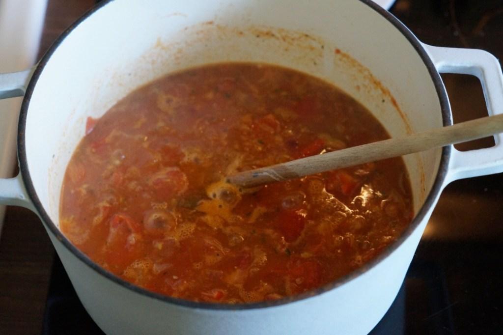 frische Tomatensuppe kocht in einem weißen Kochtopf