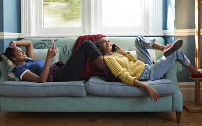 Smiling friends using phone while lying on sofa